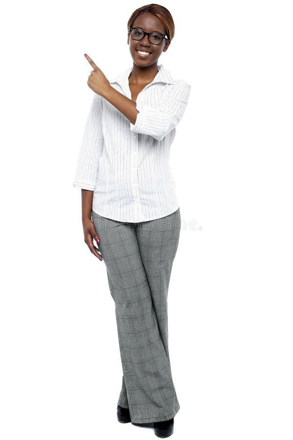 Αφρικανικός θηλυκός γραμματέας που δείχνει στο διάστημα αντιγράφων στοκ εικόνα
