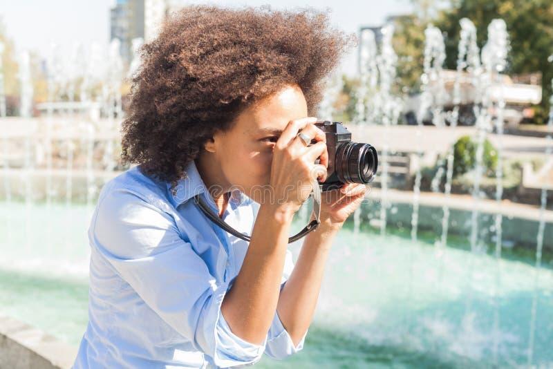 Αφρικανικός τουρίστας γυναικών που παίρνει τη φωτογραφία με την αναδρομική κάμερα υπαίθρια στοκ φωτογραφίες με δικαίωμα ελεύθερης χρήσης