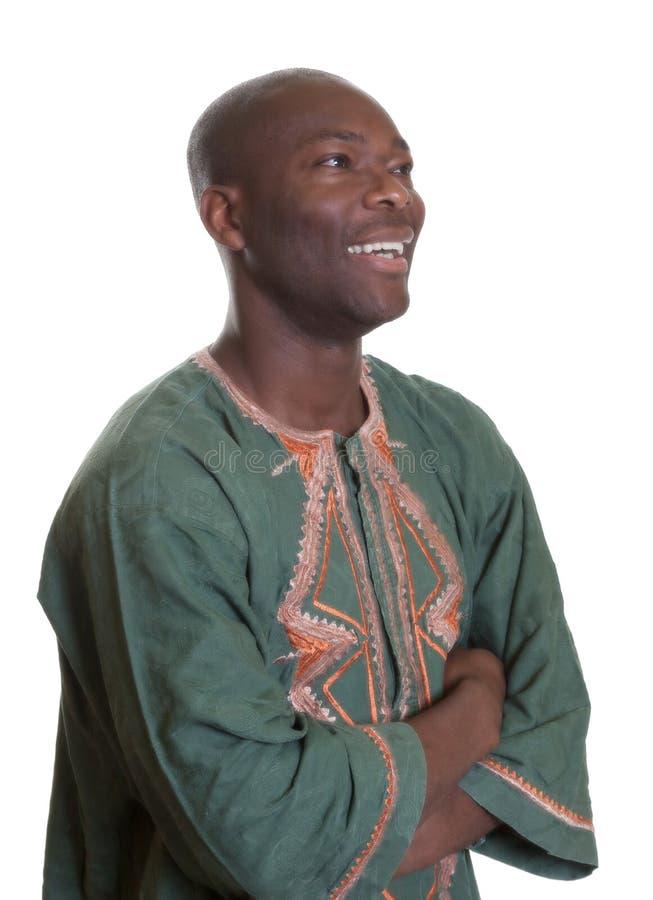 Αφρικανικό άτομο με τα παραδοσιακά ενδύματα που κοιτάζει λοξά στοκ εικόνες