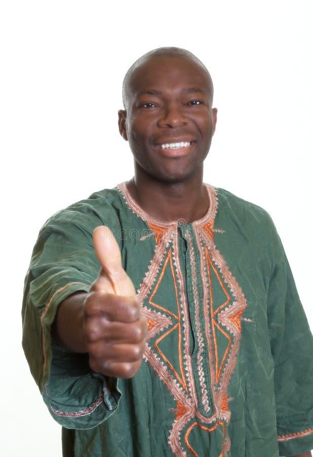 Αφρικανικό άτομο με τα παραδοσιακά ενδύματα που παρουσιάζουν αντίχειρα στοκ εικόνες