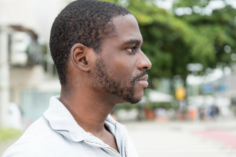 Αφρικανικό άτομο με τη γενειάδα που κοιτάζει λοξά στοκ εικόνες