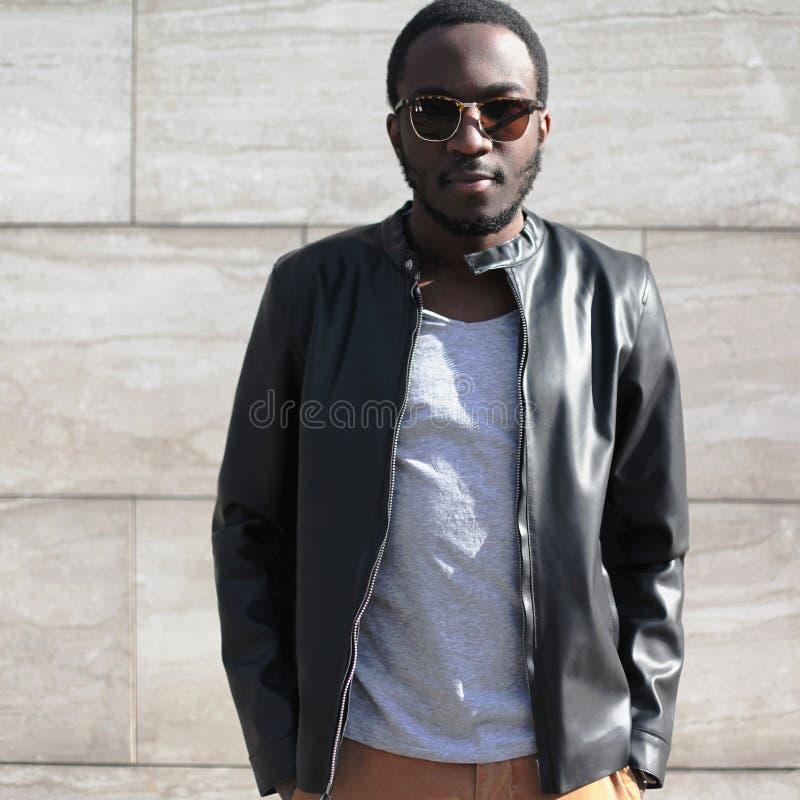Αφρικανικό άτομο μόδας που φορά τα γυαλιά ηλίου, μαύρο σακάκι δέρματος βράχου κατά τη διάρκεια του κατασκευασμένου γκρίζου βραδιο στοκ φωτογραφία