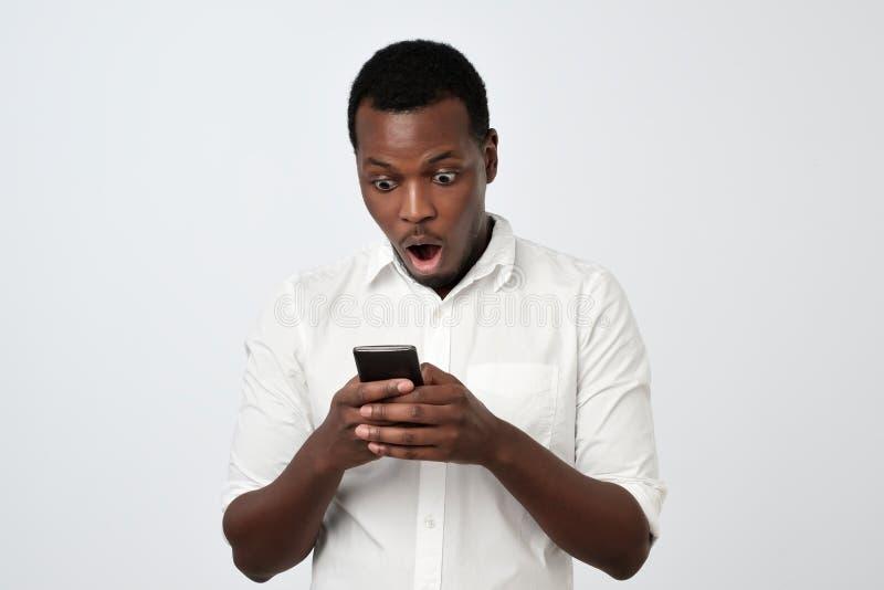 Αφρικανικό άτομο που εξετάζει το τηλέφωνο που βλέπει τις συγκλονίζοντας ειδήσεις ή τις φωτογραφίες με την έκπληκτη συγκίνηση στο  στοκ εικόνες με δικαίωμα ελεύθερης χρήσης