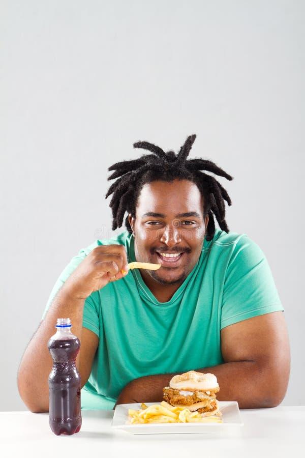 Αφρικανικό άτομο που τρώει τα τσιπ στοκ φωτογραφία με δικαίωμα ελεύθερης χρήσης