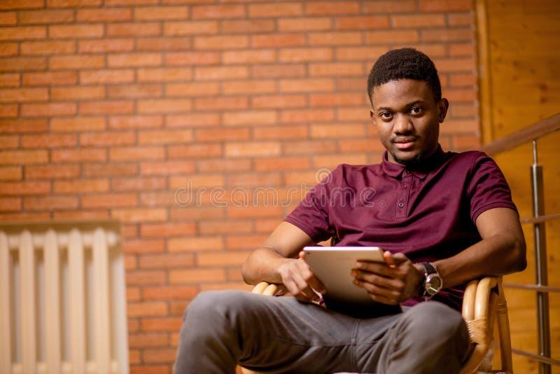 Αφρικανικό άτομο που χρησιμοποιεί την ταμπλέτα για την τηλεοπτική συνομιλία χαλαρώνοντας στην πολυθρόνα στοκ εικόνα με δικαίωμα ελεύθερης χρήσης