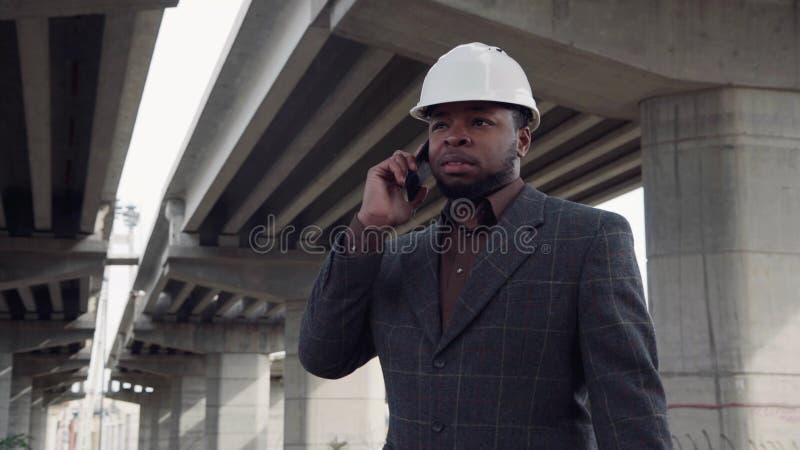 Αφρικανικό άτομο στο κράνος που μιλά στο κινητό τηλέφωνο στοκ εικόνα