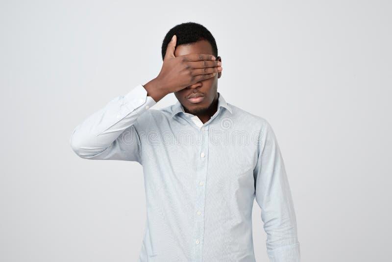 Αφρικανικό άτομο Oung στο άσπρο πουκάμισο που καλύπτει τα μάτια στοκ φωτογραφία