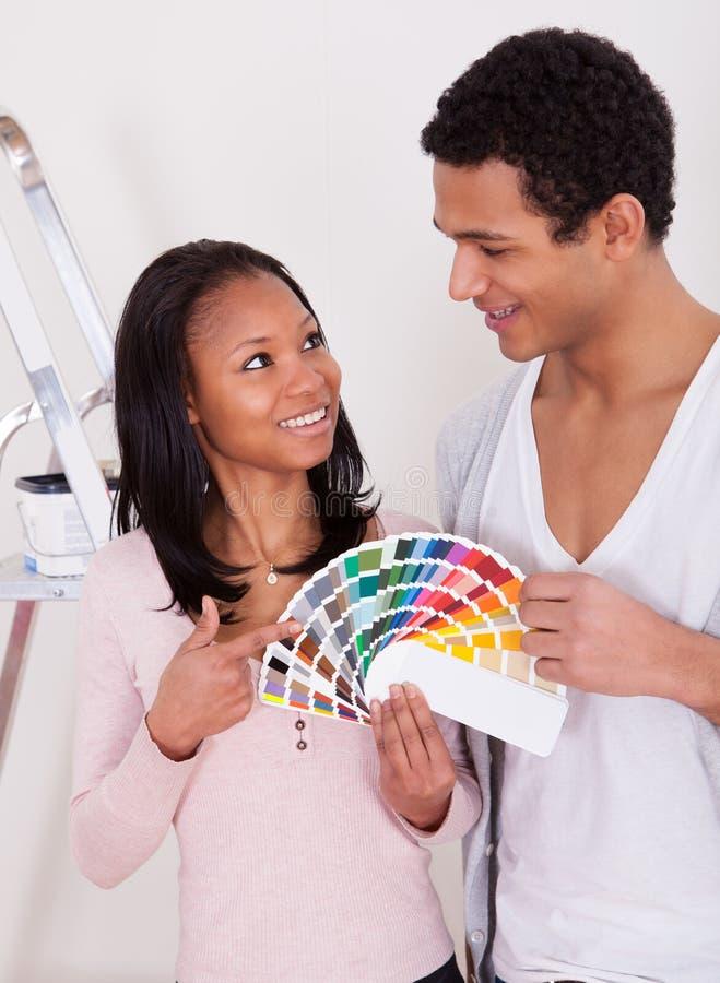 Αφρικανικό ζεύγος που επιλέγει το χρώμα για το νέο σπίτι στοκ εικόνα με δικαίωμα ελεύθερης χρήσης