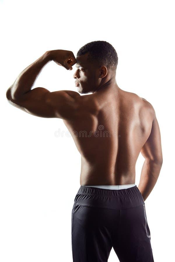 Αφρικανικό κατάλληλο άτομο που παρουσιάζει δικέφαλους μυς, όμορφο σώμα στοκ φωτογραφία με δικαίωμα ελεύθερης χρήσης