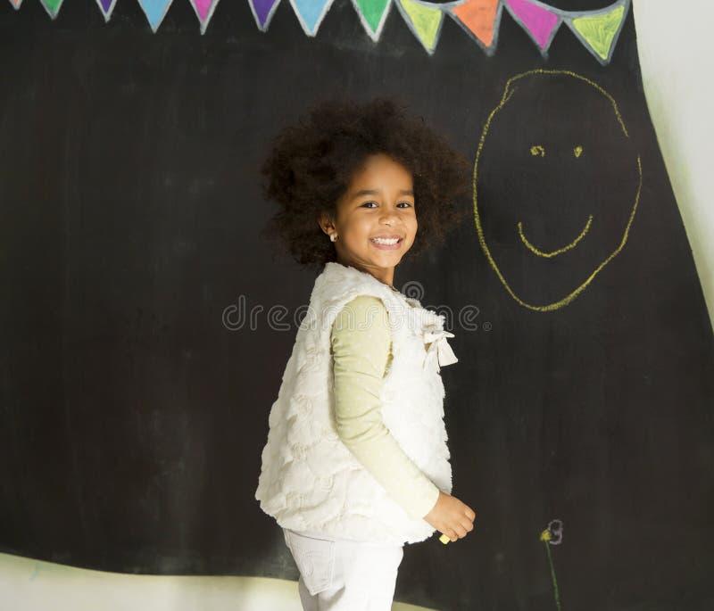 Αφρικανικό κορίτσι μπροστά από τον πίνακα στοκ εικόνες
