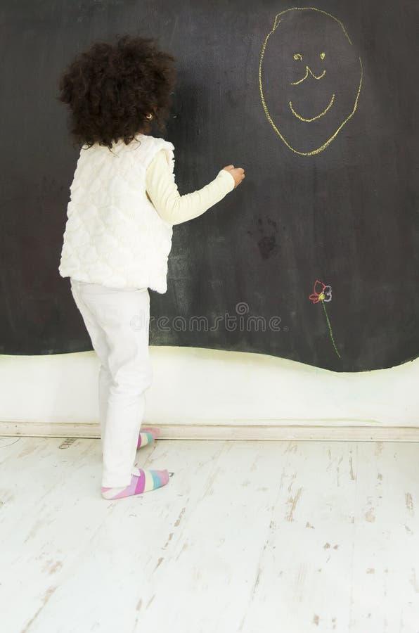 Αφρικανικό κορίτσι μπροστά από τον πίνακα στοκ φωτογραφία