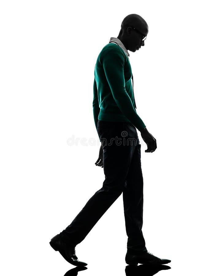 Αφρικανικό περπάτημα μαύρων που κοιτάζει κάτω από τη λυπημένη σκιαγραφία στοκ φωτογραφία
