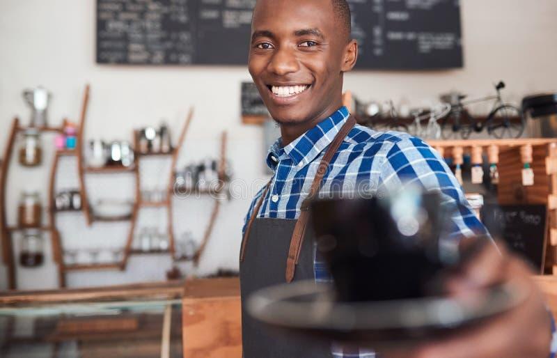 Αφρικανικό barista χαμόγελου που προσφέρει επάνω ένα φρέσκο φλυτζάνι του cappuccino στοκ φωτογραφίες