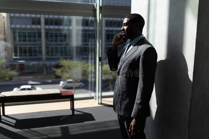 Αφροαμερικάνος του επιχειρηματία που μιλά στο κινητό τηλέφωνο στην αρχή στοκ φωτογραφίες με δικαίωμα ελεύθερης χρήσης
