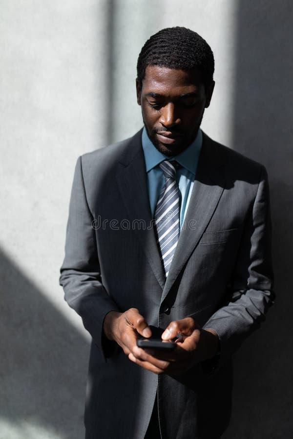 Αφροαμερικάνος του επιχειρηματία που χρησιμοποιεί το κινητό τηλέφωνο στην αρχή στοκ εικόνα