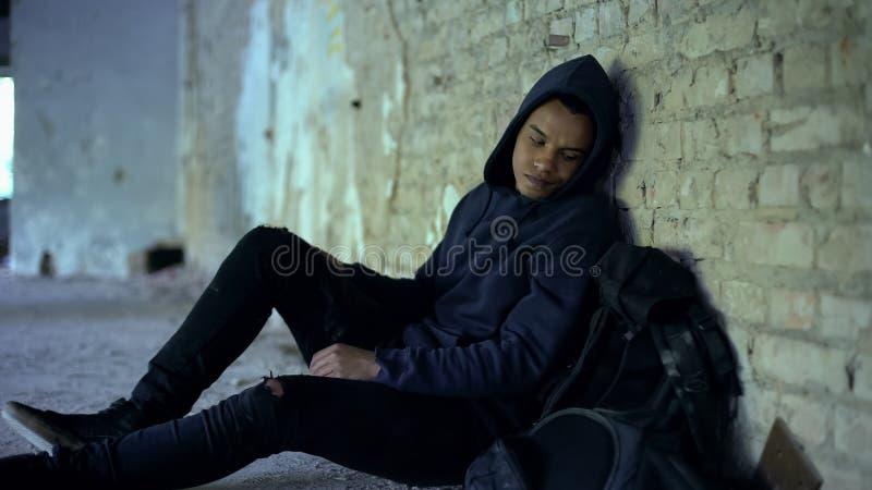 Αφροαμερικανός κρύψιμο εφήβων από τη φοβέρα στο εγκαταλειμμένο κτήριο, ρατσισμός στοκ φωτογραφία με δικαίωμα ελεύθερης χρήσης