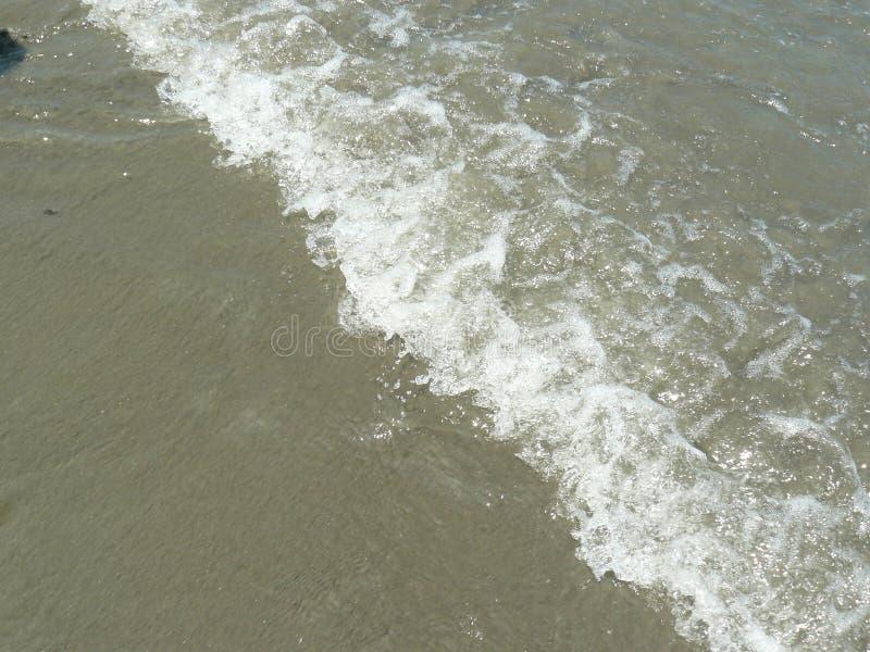 Αφρός από ένα κύμα πέρα από την άμμο στοκ φωτογραφία