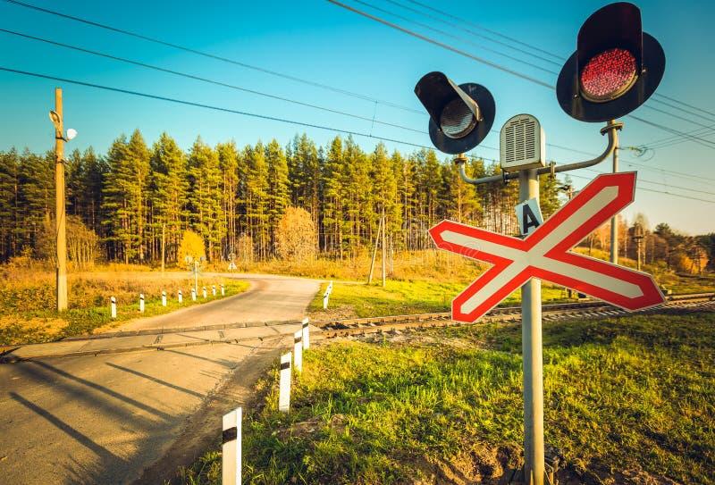 Αφύλακτο πέρασμα σιδηροδρόμων και κόκκινος φωτεινός σηματοδότης με το οδηγημένο και υγιές κιβώτιο ομιλητών στο σιδηρόδρομο σε ένα στοκ εικόνα