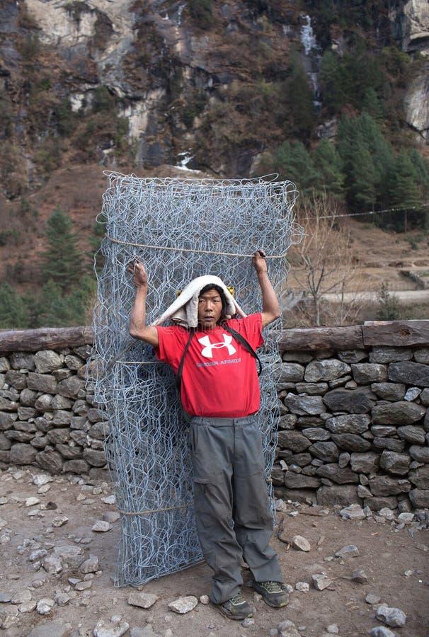Αχθοφόρος που φέρνει ένα βαρύ φορτίο στο Νεπάλ Ιμαλάια στοκ εικόνες με δικαίωμα ελεύθερης χρήσης