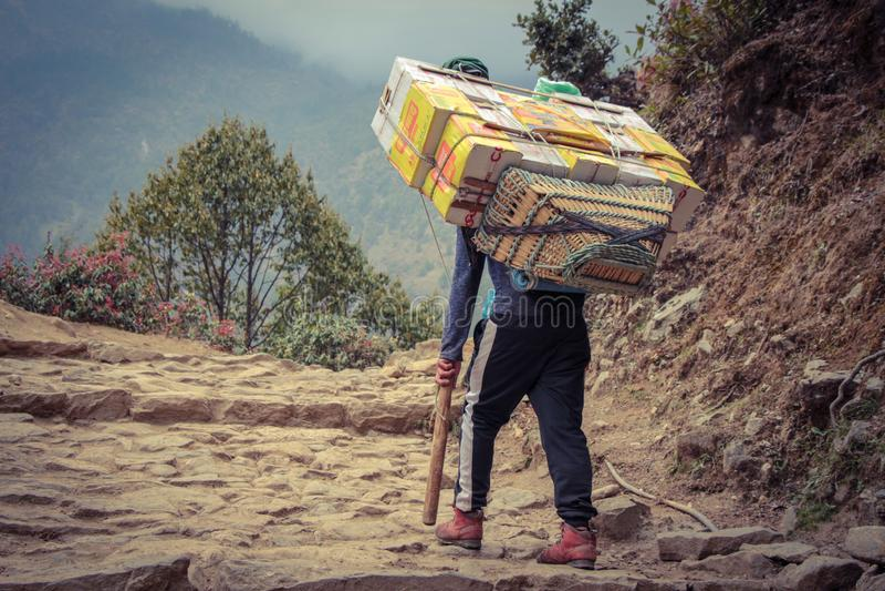 Αχθοφόρος Sherpa που φέρνει ένα βαρύ φορτίο στο Νεπάλ στοκ φωτογραφίες