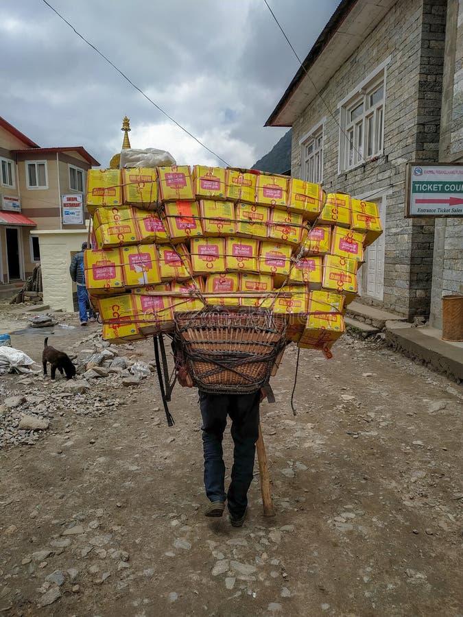 Αχθοφόρος Sherpa που φέρνει ένα βαρύ φορτίο στο Νεπάλ στοκ εικόνες