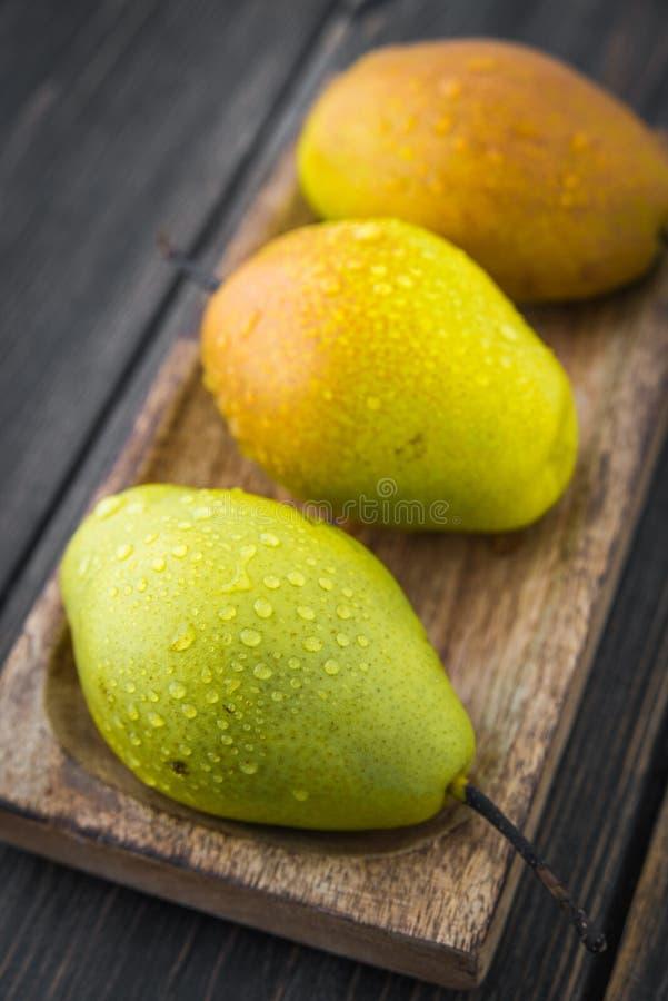 Αχλάδια διαφορετικό ripeness στο καφετί ξύλινο πιάτο τεχνών στοκ φωτογραφία με δικαίωμα ελεύθερης χρήσης
