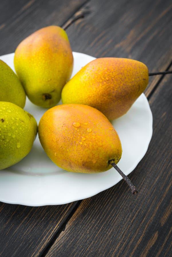 Αχλάδια του Ουίλιαμς διαφορετικό ripeness στο άσπρο κυκλικό πιάτο στοκ φωτογραφία