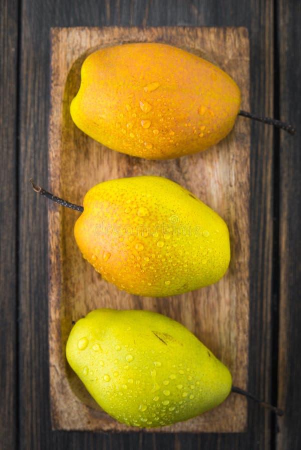 Αχλάδια των ποικιλιών βαθμών ripeness στο καφετί ξύλινο πιάτο τεχνών στοκ φωτογραφίες