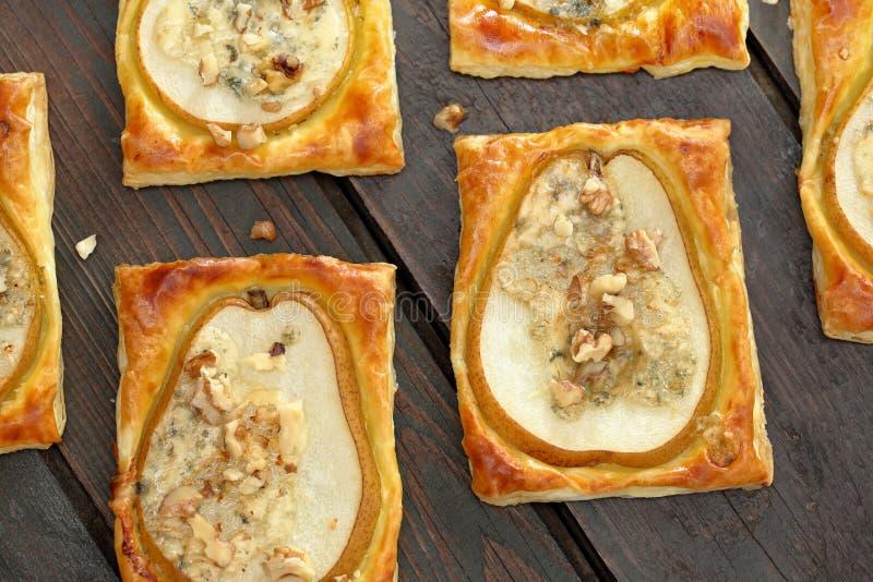 Αχλάδια που ψήνονται στη ζύμη ριπών με gorgonzola το τυρί και τα ξύλα καρυδιάς στοκ εικόνα με δικαίωμα ελεύθερης χρήσης
