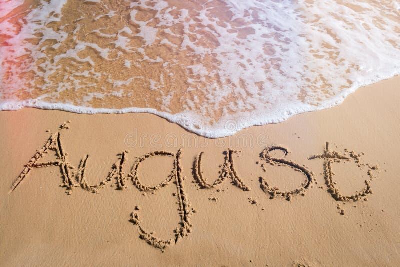 Αύγουστος που γράφεται στην άμμο παραλιών στοκ εικόνες