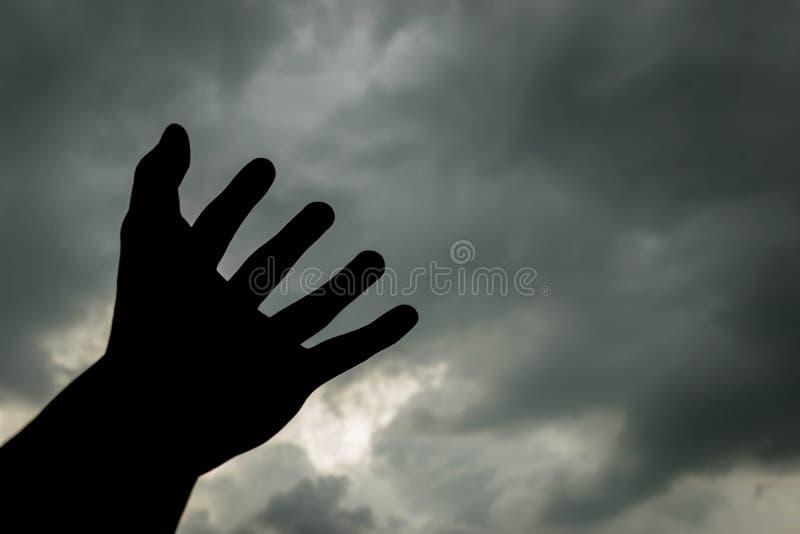 Αύξηση του χεριού στο σκοτεινό νεφελώδη ουρανό στη σκιαγραφία στοκ εικόνες
