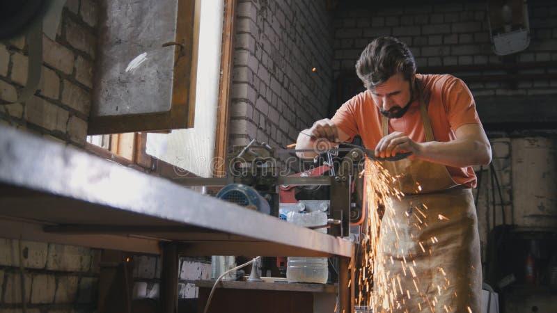 Αλέθοντας εργαλεία μετάλλων με τα σπινθηρίσματα - σφυρηλατήστε το εργαστήριο στοκ φωτογραφίες