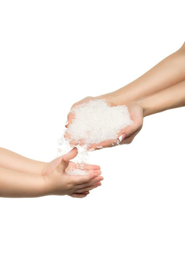Αλατισμένα κρύσταλλα θάλασσας στο χέρι γυναικών και το χέρι παιδιών στοκ φωτογραφίες