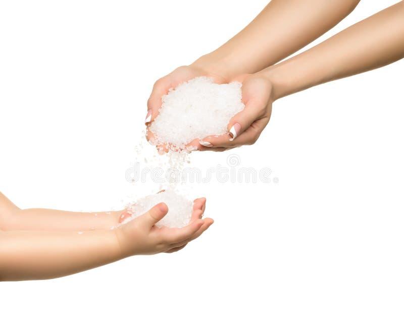 Αλατισμένα κρύσταλλα θάλασσας στο χέρι γυναικών και το χέρι παιδιών στοκ φωτογραφία με δικαίωμα ελεύθερης χρήσης
