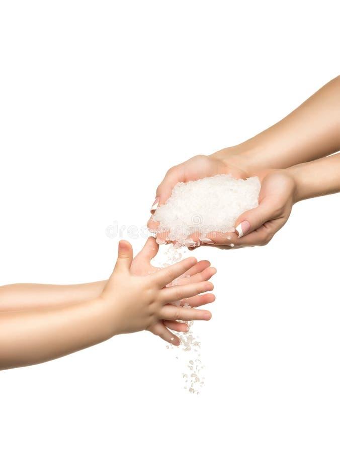 Αλατισμένα κρύσταλλα θάλασσας στο χέρι γυναικών και το χέρι παιδιών στοκ εικόνες