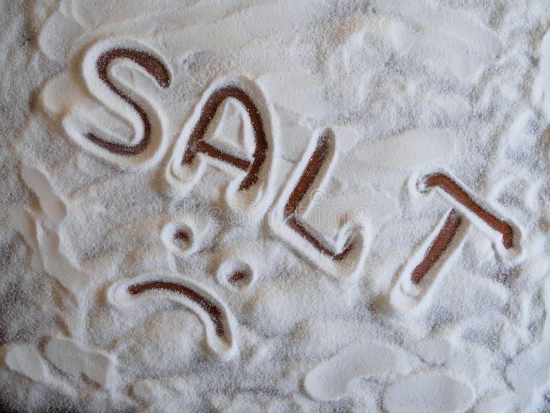 Αλατισμένη επιγραφή σε έναν σωρό του άσπρου μαγειρεύοντας άλατος σε ένα ξύλινο υπόβαθρο πρόσωπο λυπημένο στοκ φωτογραφίες
