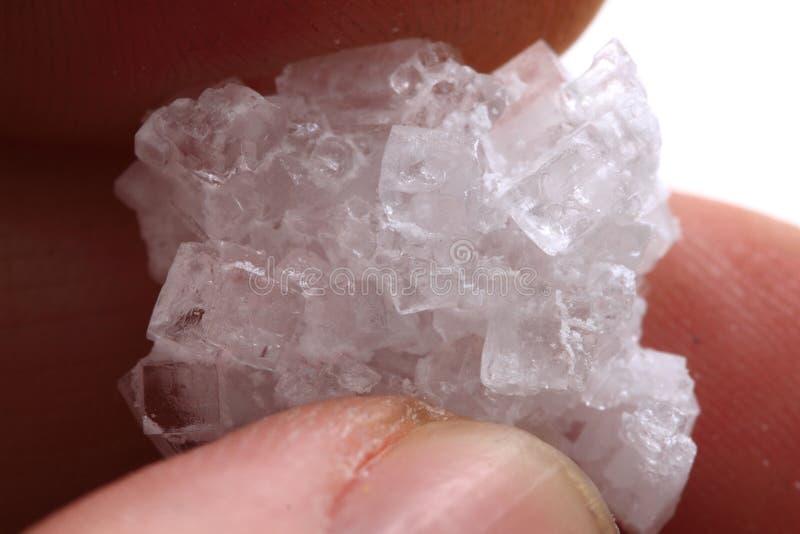 Αλατισμένο κρύσταλλο στο ανθρώπινο χέρι στοκ φωτογραφία