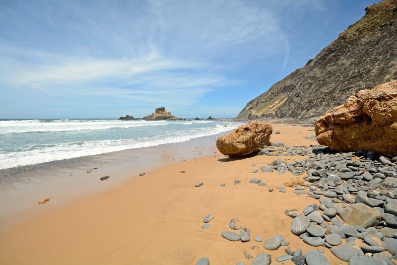 Αλγκάρβε: Βράχοι στην παραλία Praia do Castelejo κοντά σε Sagres, Πορτογαλία Surfer στοκ εικόνες