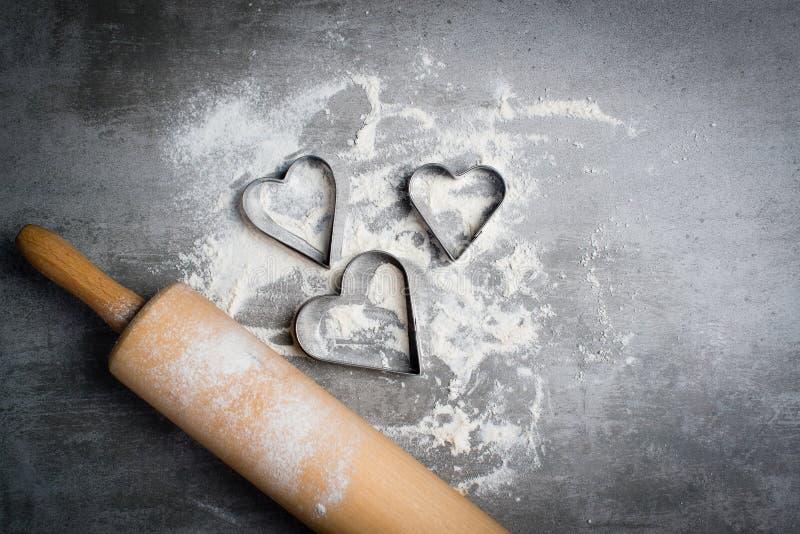 Αλεύρι, κόπτες μπισκότων που διαμορφώνονται ως καρδιά και κυλώντας καρφίτσα σε μια πέτρα στοκ φωτογραφία