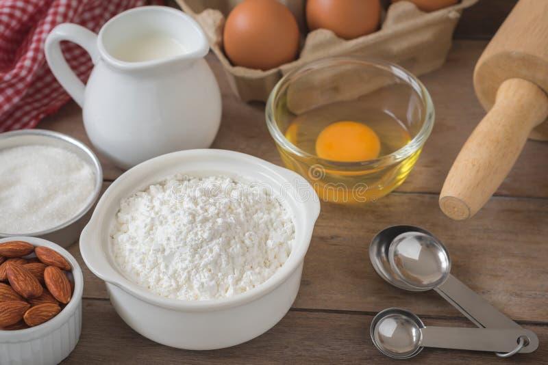 Αλεύρι συστατικών ψησίματος, αυγό, γάλα, αμύγδαλα, ζάχαρη στο ξύλινο TA στοκ εικόνες