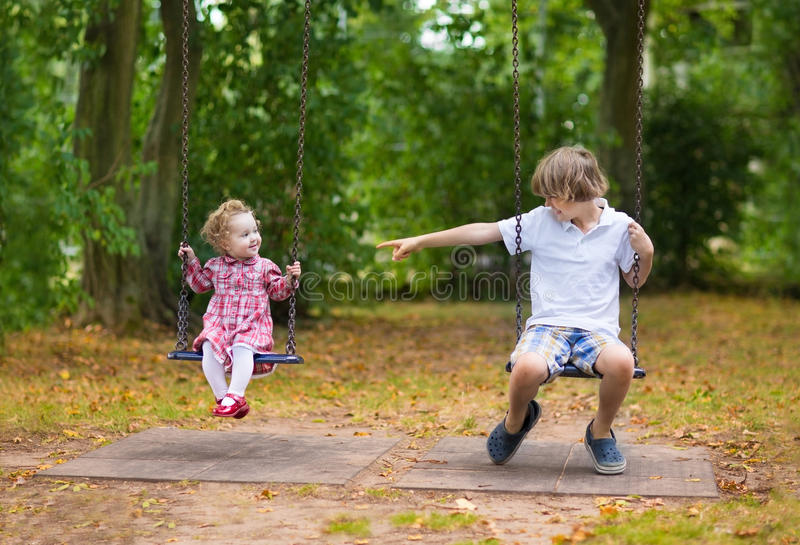 Αδελφή αδελφών και μωρών στην ταλάντευση στην παιδική χαρά στοκ φωτογραφία