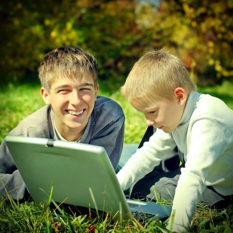 Αδελφοί με το lap-top στοκ εικόνα με δικαίωμα ελεύθερης χρήσης