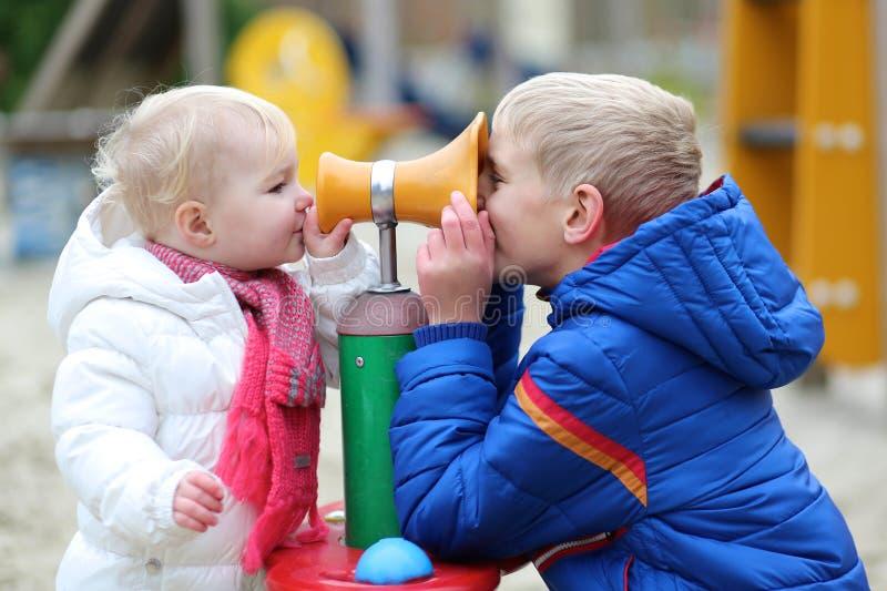 Αδελφός και αδελφή που έχουν τη διασκέδαση μαζί στην παιδική χαρά στοκ φωτογραφίες