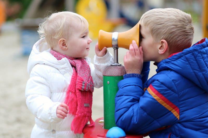 Αδελφός και αδελφή που έχουν τη διασκέδαση μαζί στην παιδική χαρά στοκ εικόνα με δικαίωμα ελεύθερης χρήσης