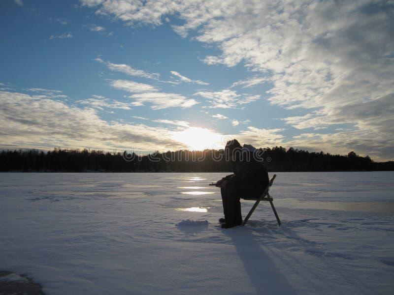 Αλιεία πάγου ηλιοβασιλεμάτων στοκ εικόνα
