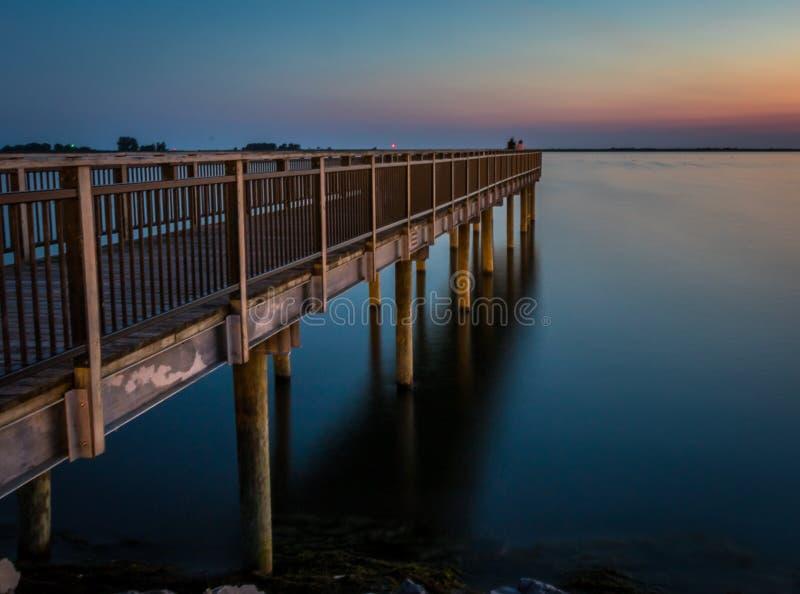 Αλιεία της αποβάθρας πέρα από τη λίμνη Erie στο ηλιοβασίλεμα στοκ εικόνες με δικαίωμα ελεύθερης χρήσης