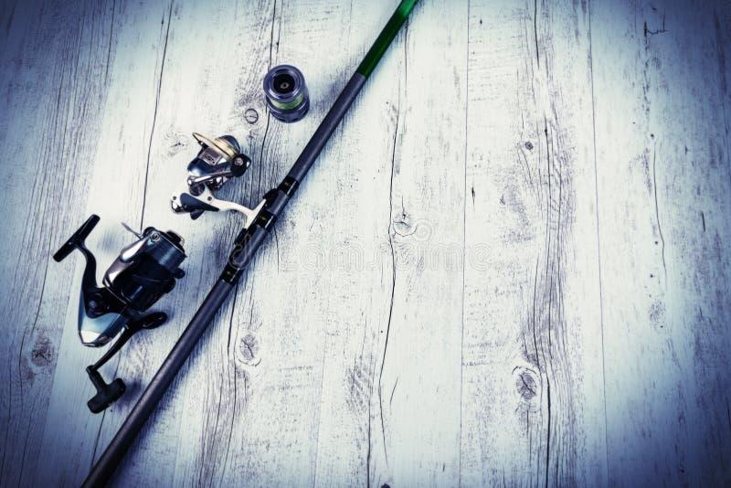 Αλιεύοντας τον εξοπλισμό - περιστροφή, γάντζοι και θέλγητρα αλιείας στο άσπρο ξύλινο υπόβαθρο Τοπ όψη στοκ εικόνες