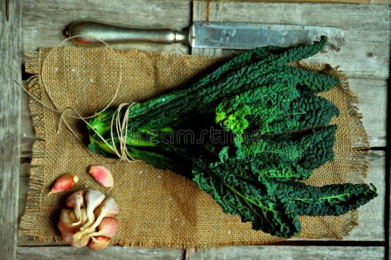 Αλκαλικά, υγιή τρόφιμα: φύλλα κατσαρού λάχανου σε ένα εκλεκτής ποιότητας υπόβαθρο στοκ εικόνες