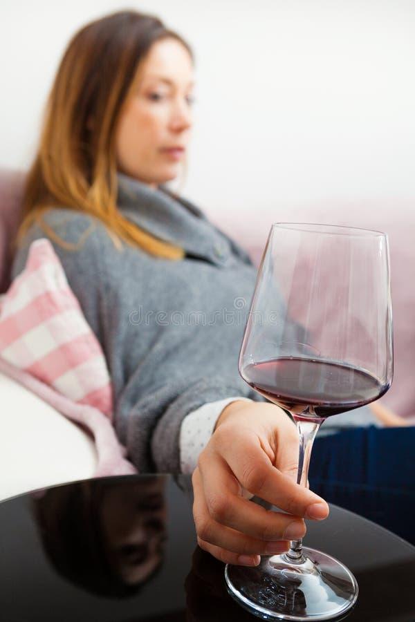 Αλκοολισμός, γυναίκα εθισμού οινοπνεύματος Να χαλαρώσει στο σπίτι με το κόκκινο κρασί στοκ φωτογραφία με δικαίωμα ελεύθερης χρήσης
