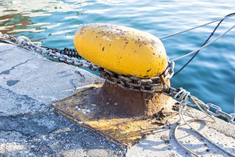 Αλυσίδα που δένεται σε έναν στυλίσκο Σχοινί πρόσδεσης που τυλίγεται γύρω από τη σφήνα στο υπόβαθρο θάλασσας Εργάτης μετάλλων στο  στοκ φωτογραφία με δικαίωμα ελεύθερης χρήσης